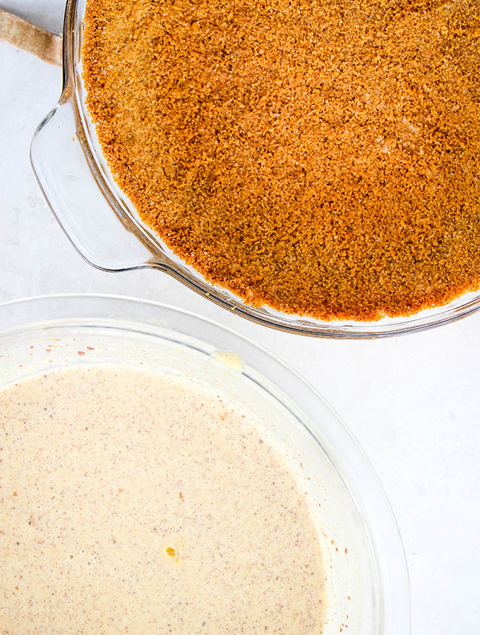 The graham cracker crust is baked and the pumpkin pie filling is mixed before they are combined.
