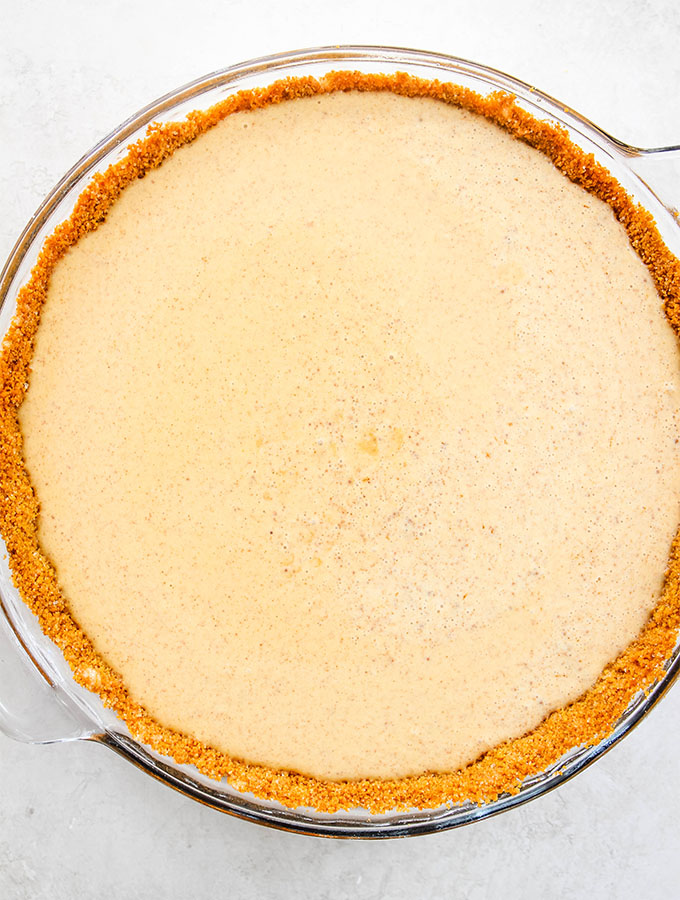 Pumpkin pie filling is poured into a pre baked pie crust before it is placed in the oven.