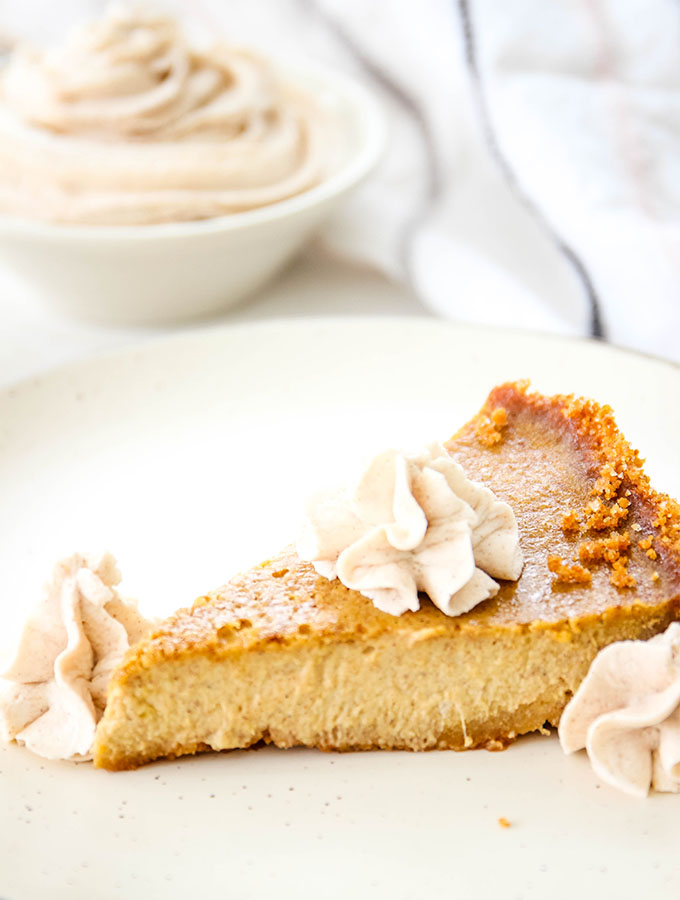 Pumpkin pie is plated on a white plate with whipped cream in a bowl in the backgroud.