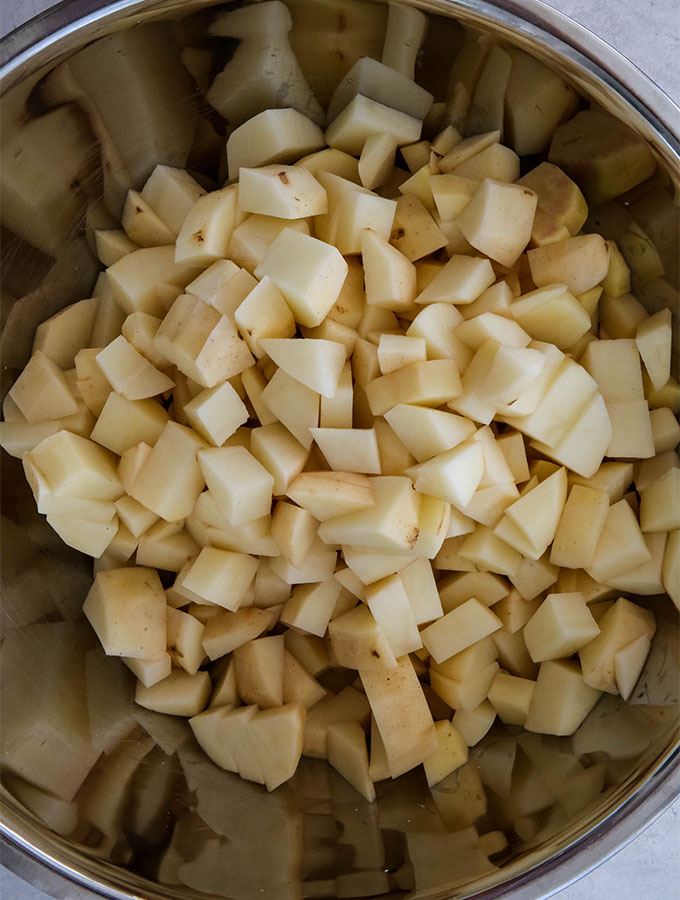 Russet potatoes are peeled and diced into small bite sized pieces before they are boiled.