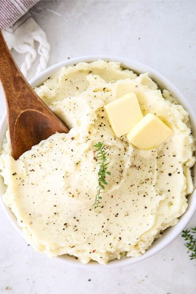 Mashed potatoes are plated in a white bowl with a large wooden spoon spooning some out.