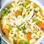 Chicken tortellini soup is plated in a white bowl and topped with fresh parsley for extra flavor.