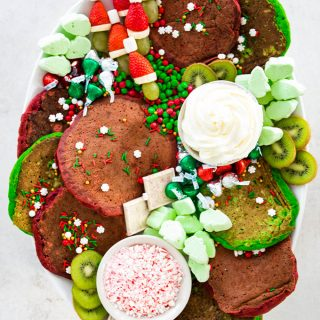 A Christmas breakfast board is filled with pancakes, fruits, candies, and homemade whipped cream.