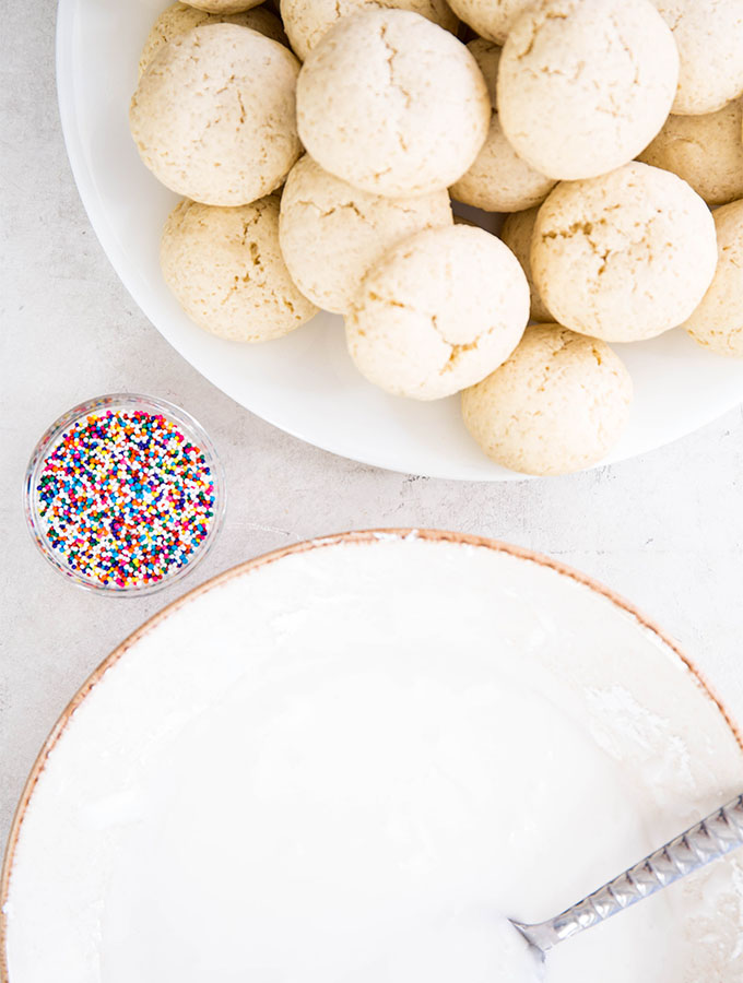 Italian anise cookies are about to be dunked in a sugar glaze and topped with sprinkles.