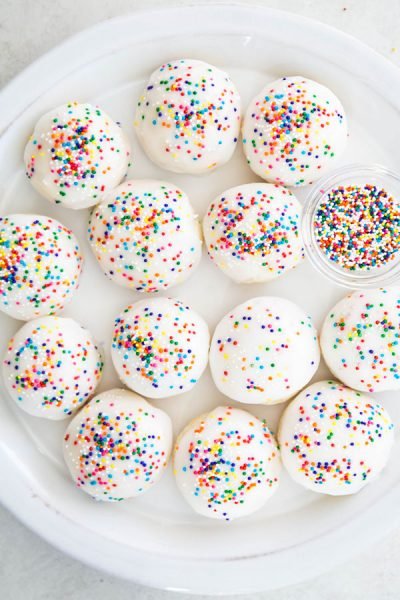 Italian anise cookies are plated on a white plate next to a small bowl of sprinkles.