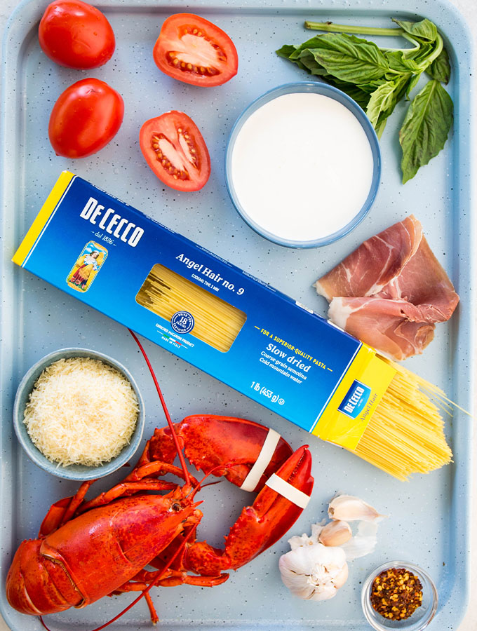 Lobster pasta is made with pasta, lobster, basil. prosciutto, tomatoes, etc.