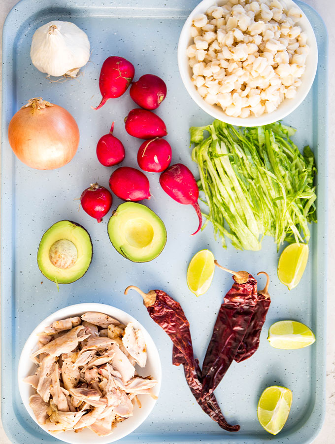 Turkey pozole ingredients are displayed individually on a blue baking sheet.