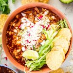 Red pozole is plated in a red bowl and topped with lettuce, radishes, limes, cheese, and chips.