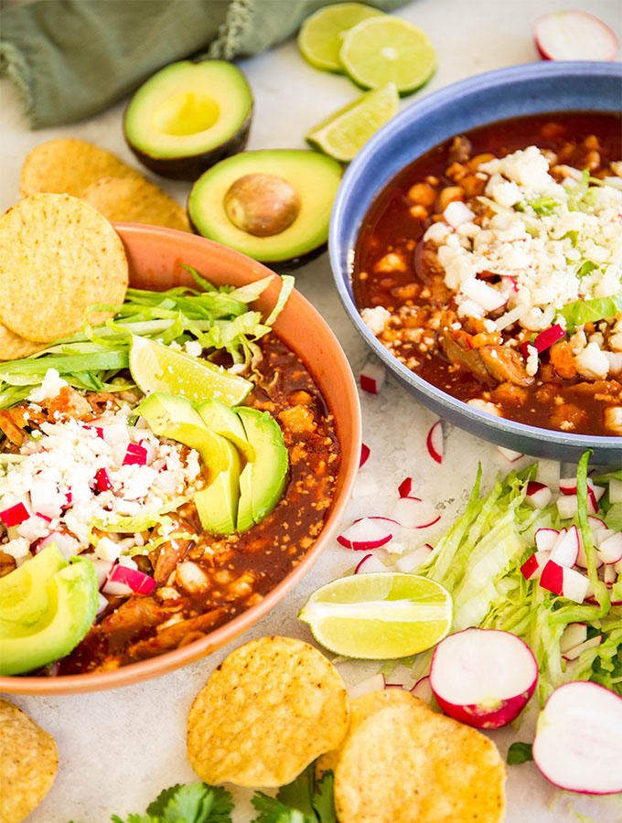 Turkey pozole is plated in two bowls with toppings like avocados, radishes. chips, and cheese.
