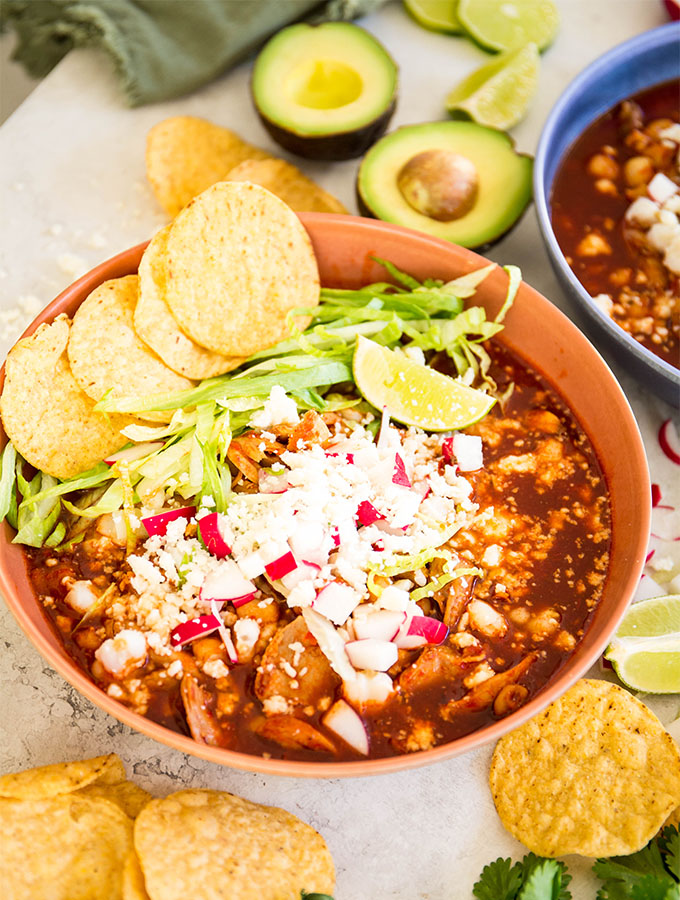 Red pozole is plated in a red bowl and topped with chips, radishes, cheese, and lettuce.