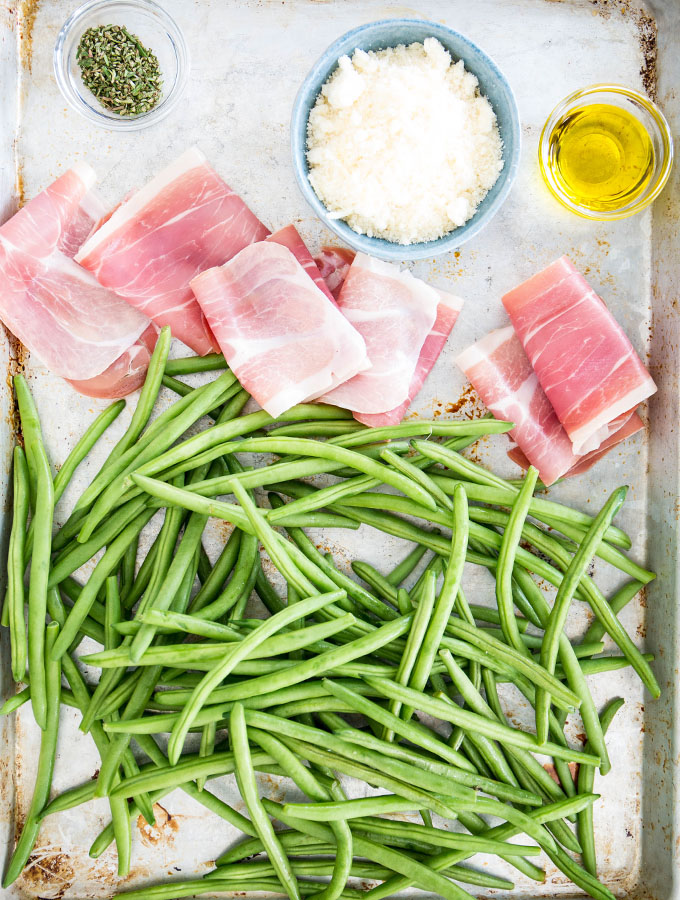 Prosciutto wrapped green bean ingredients are displayed individually on a baking sheet.
