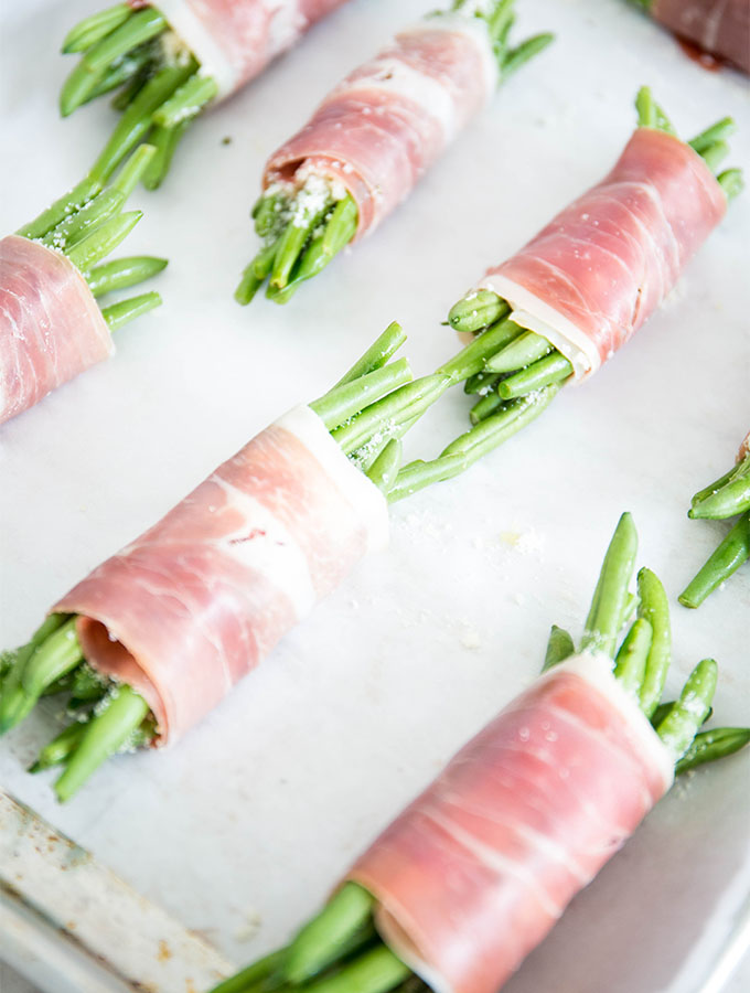 Green beans are wrapped in prosciutto and placed on a parchment paper lined baking sheet.