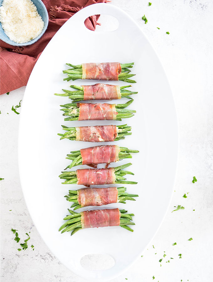 Prosciutto wrapped green bean bundles are plated on a white plate next to a red napkin.