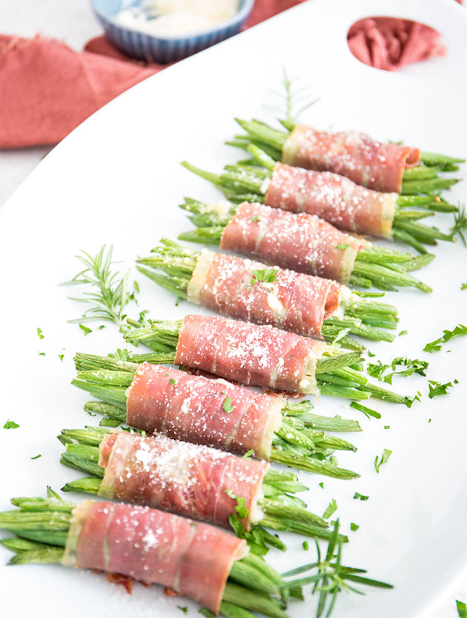 Prosciutto wrapped green bean bundles are plated on a white plate and topped with parmesan cheese.