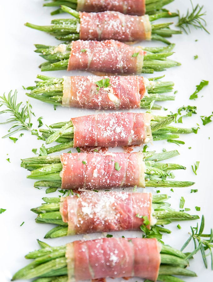 Prosciutto wrapped green beans are plated on a white plate and topped with fresh parsley and parmesan cheese.
