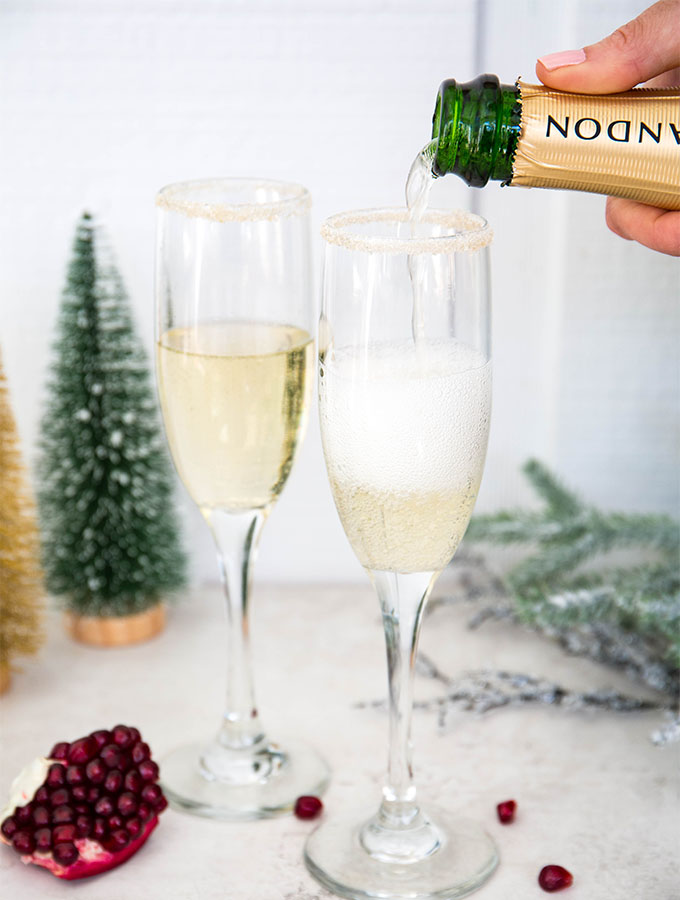 A hand is pouring the champagne into the sugar rimmed flutes.