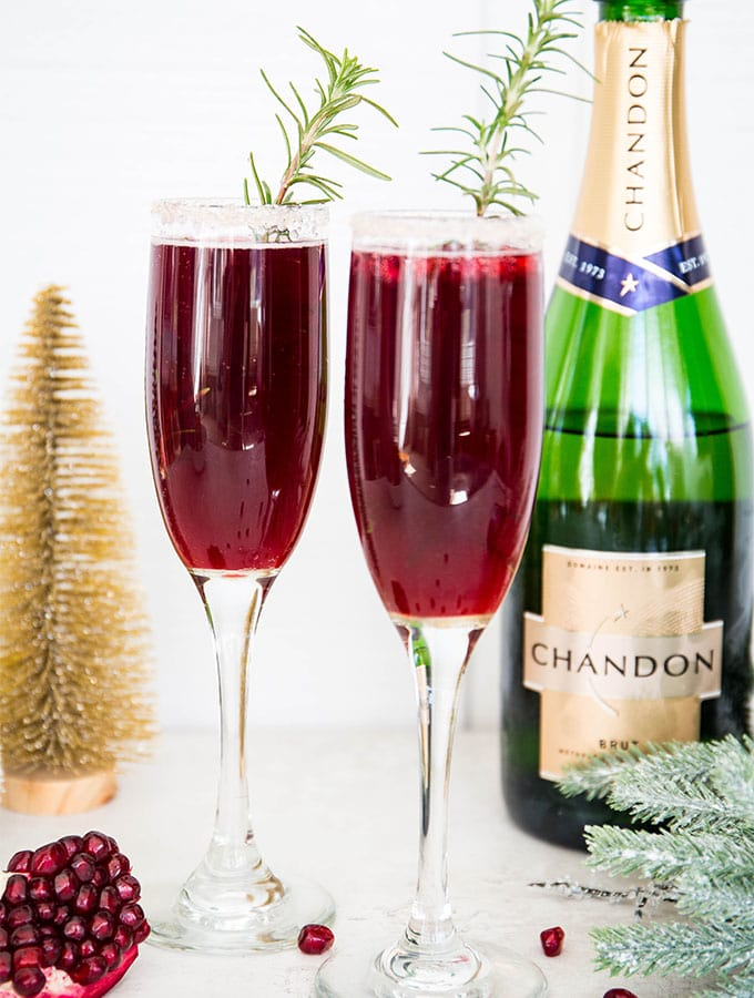 Pomegranate mimosas are placed in front of a bottle of Chandon champagne.