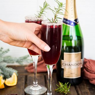 A hand is reaching for a champagne flute that is garnished with rosemary.