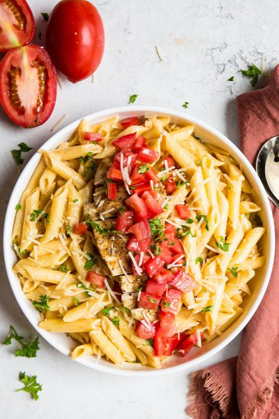 Cajun Chicken Pasta is plated in a white bowl and placed next to tomatoes, a napkin, and forks.
