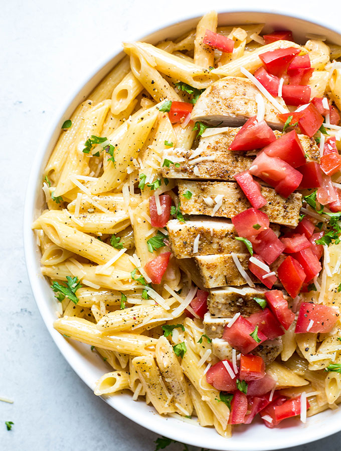 Creamy cajun chicken pasta is plated in a white bowl and topped with tomatoes and cheese.