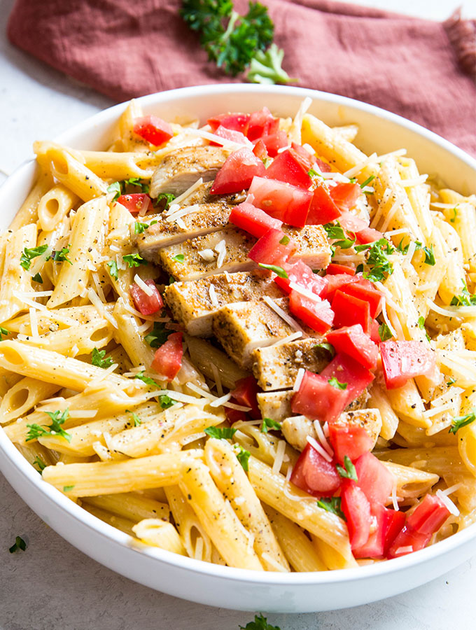 Cajun chicken and pasta is plated in a white bowl next to a red napkin and topped with tomatoes and cheese.