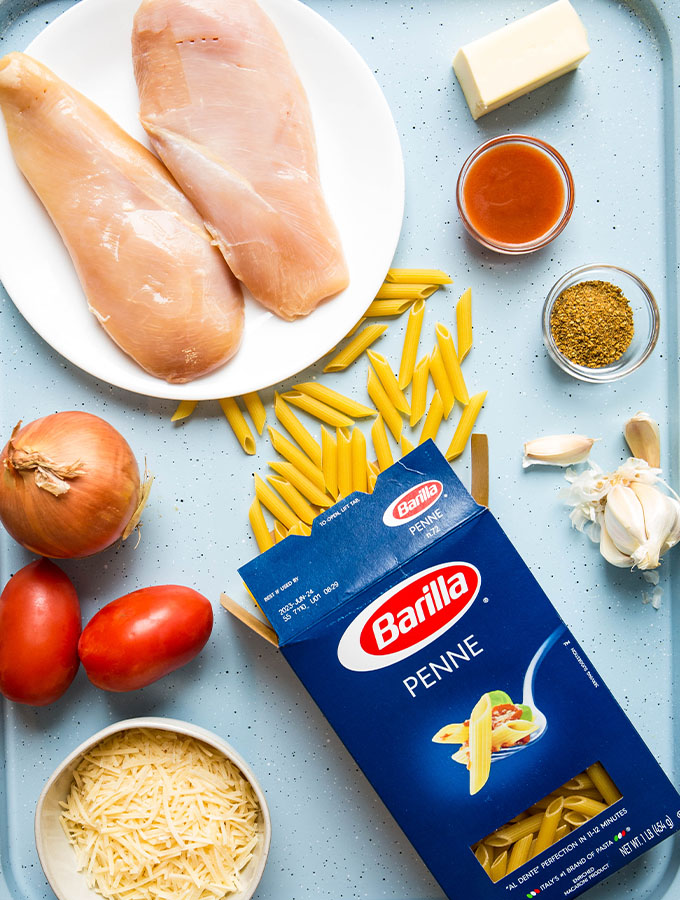 Cajun chicken pasta ingredients are placed individually on a blue baking sheet.