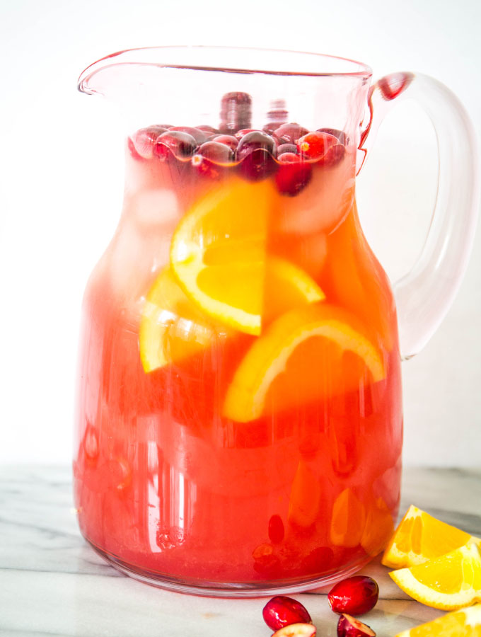 Cranberry white wine sangria is made in a pitcher and topped with fresh cranberries and oranges.