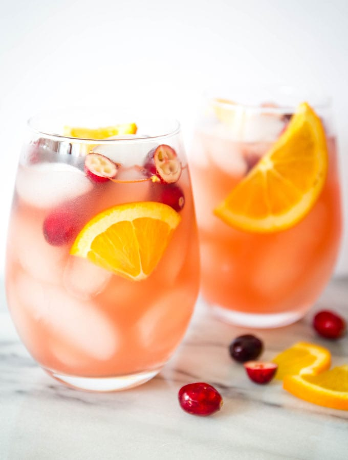 Two wine glasses are full of ice and sangria and topped with oranges and cranberries.