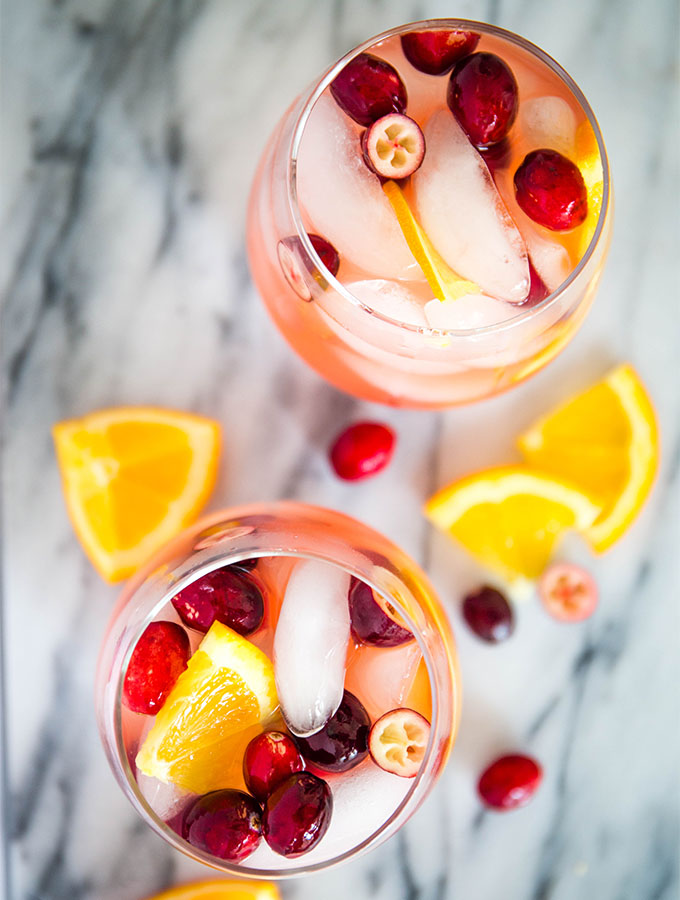 Two wine glasses are topped with ice, sangria, and garnishes of orange wedges.
