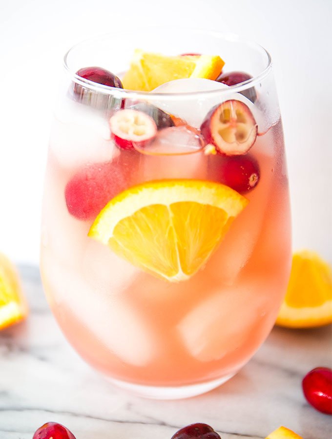 White wine sangria is poured into a wine glass and topped with fresh garnishes.