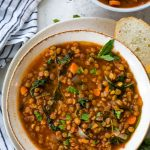 Lentil soup is plated in a large bowl next to sliced Italian bread and a napkin.