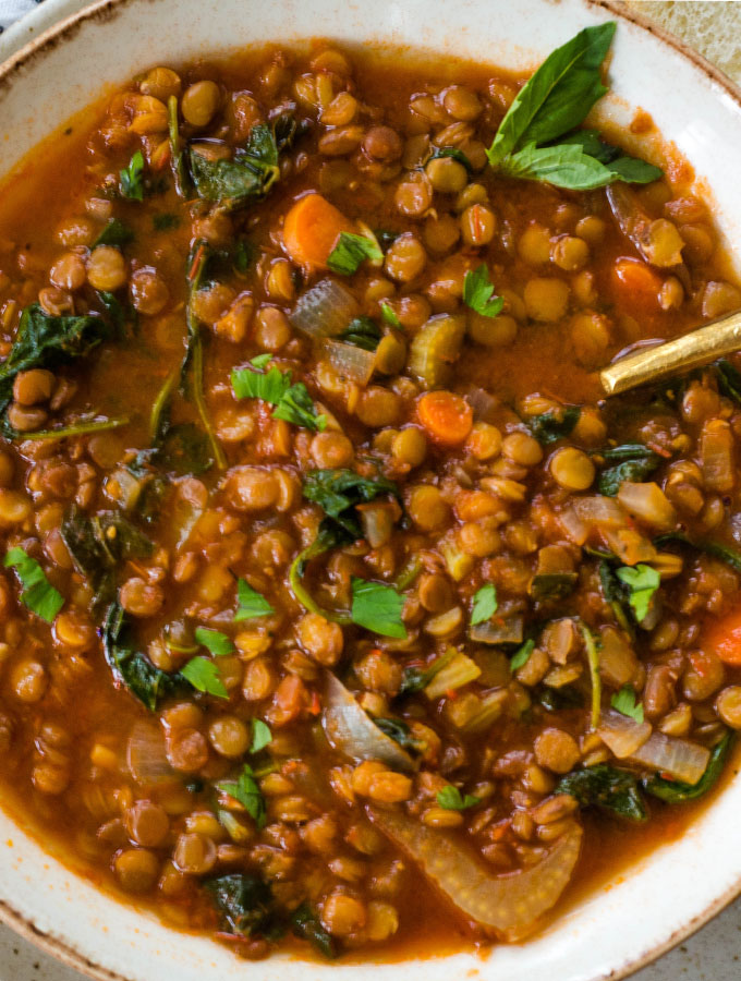 Lentil soup is plated in a white bowl and topped with a small sprig of fresh basil.