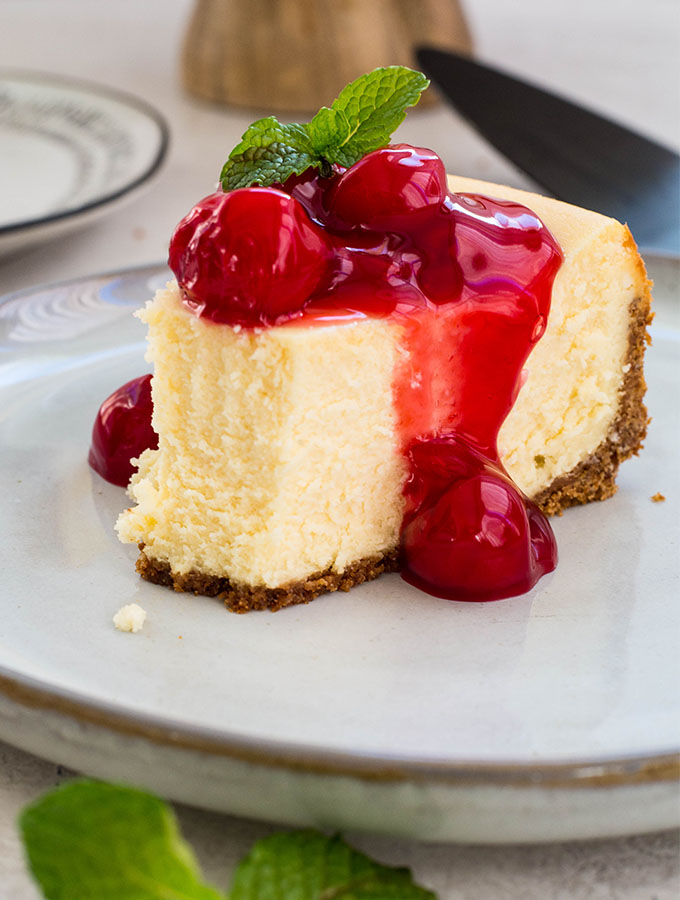 The slice of cheesecake has a bite taken out of it to show the fluffy texture.