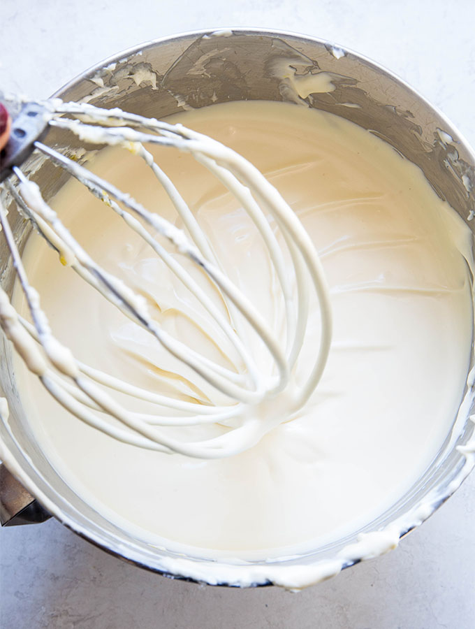 Cheesecake filling is whipped in a mixing bowl until is is creamy and silky.
