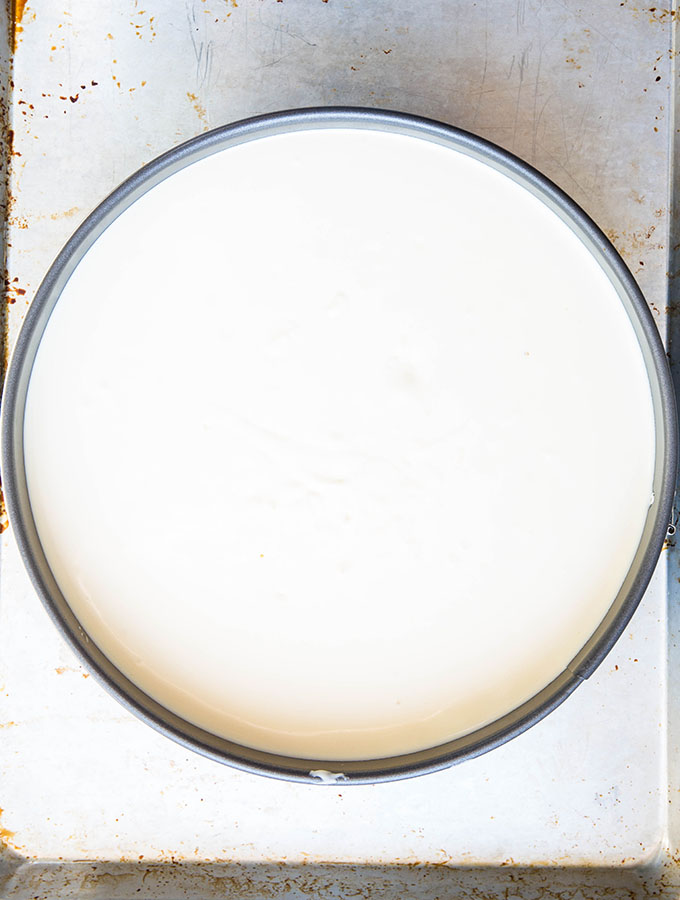 The cheesecake filling is poured into the springform pan after the crust is baked first.
