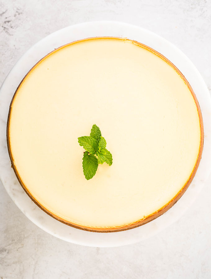 The cheesecake is topped with a sprig of mint to beautifully garnish the cake.