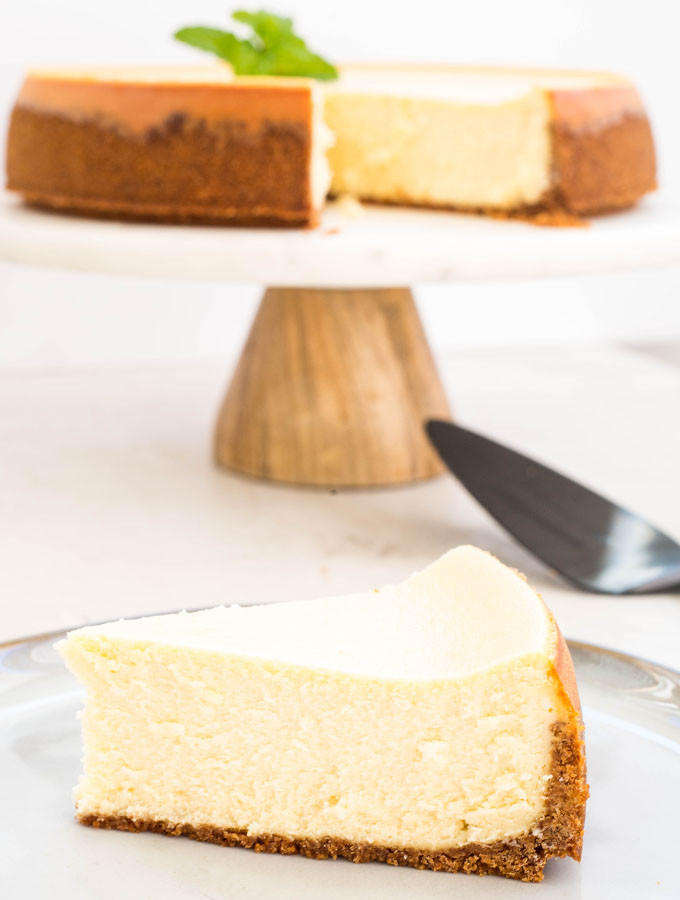 A slice of cheesecake is plated in front of the cheesecake on a cakestand.