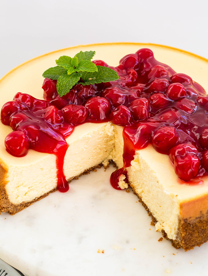 Cherry pie filling tops a sliced cheesecake and topped with mint.
