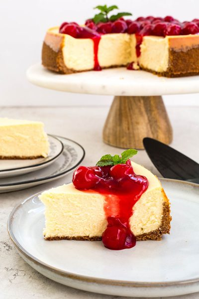 The slice of cheesecake is topped with cherry pie filling and a sprig of mint.