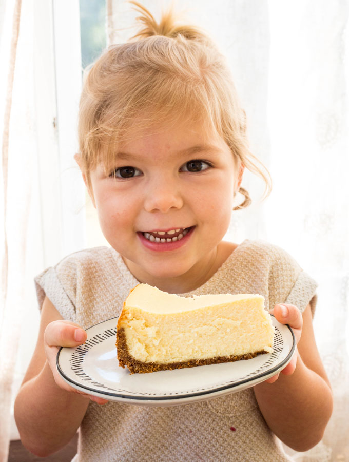 Evelyn is holding a plate with a cheesecake slice on it and is smiling wide!