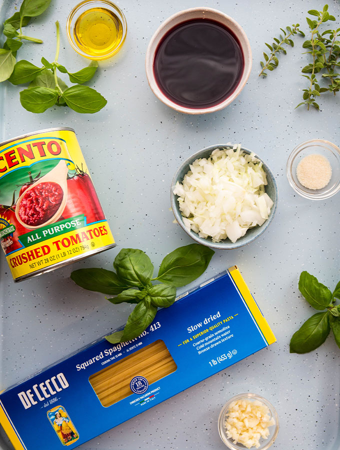 Red wine pasta sauce ingredients include crushed tomatoes, onions, garlic, wine, and herbs.