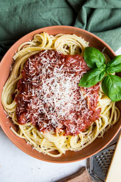 Spaghetti pasta is topped with red wine pasta sauce to show it's thick texture and deep color.