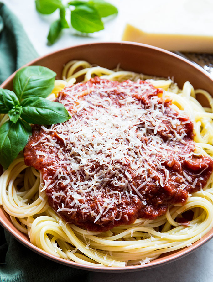 Red wine sauce is covering spaghetti and is topped with parmesan cheese and basil.