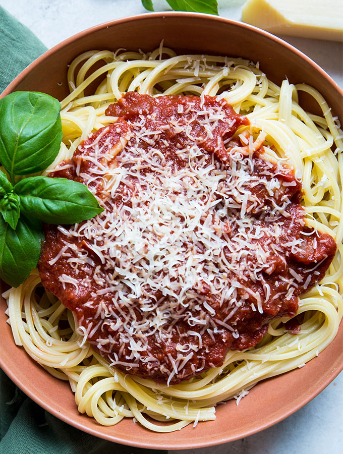 Red wine pasta sauce is placed on top of the spaghetti pasta and is plated in a red bowl.