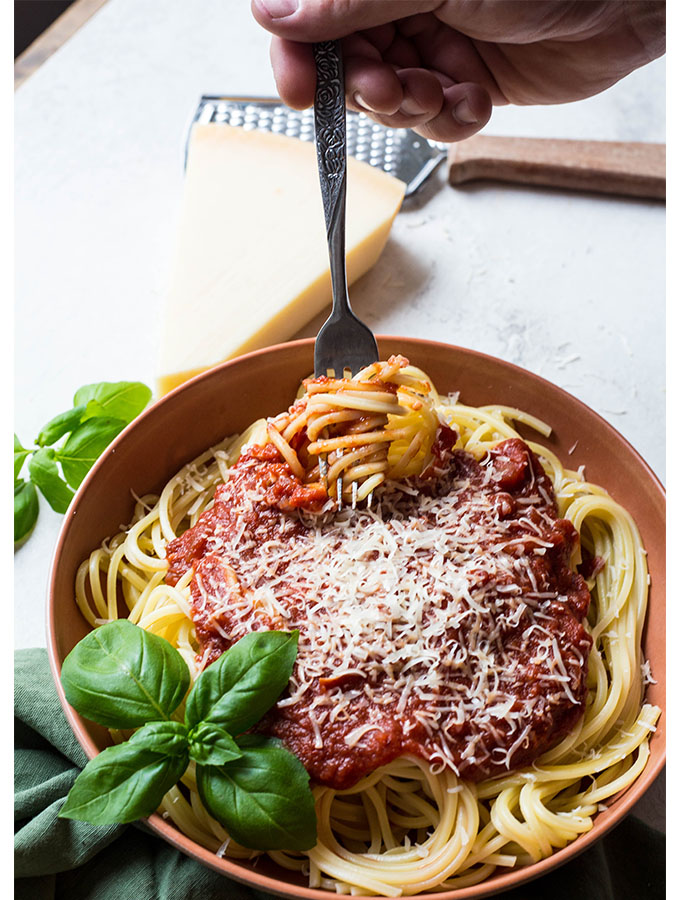 A hand is twirling a fork in the spaghetti pasta to show how the sauce sticks to the pasta.