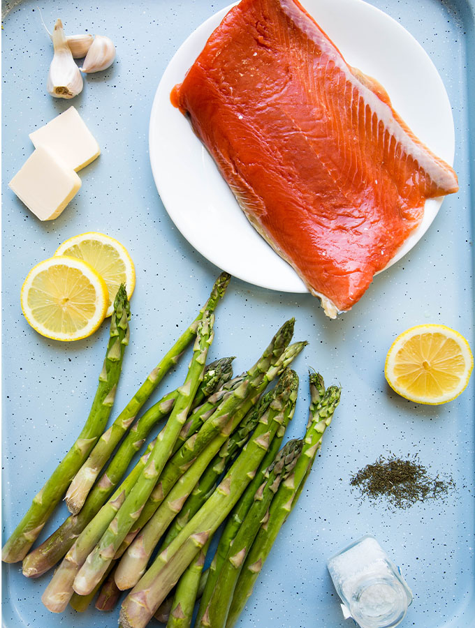 Salmon and asparagus ingredients are displayed individually on a baking sheet.