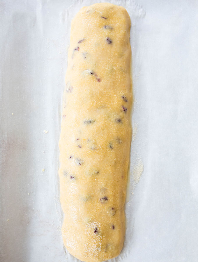 A loaf of biscotti dough is placed on a baking sheet, egg washed, and sprinkled with sugar before baking.