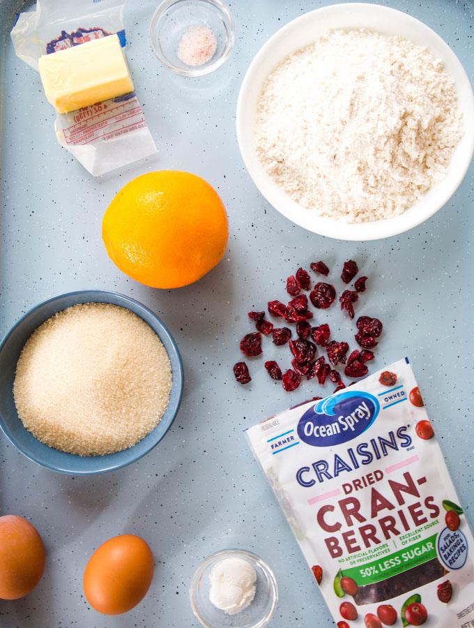 Cranberry orange biscotti ingredients are displayed individually on a baking sheet.