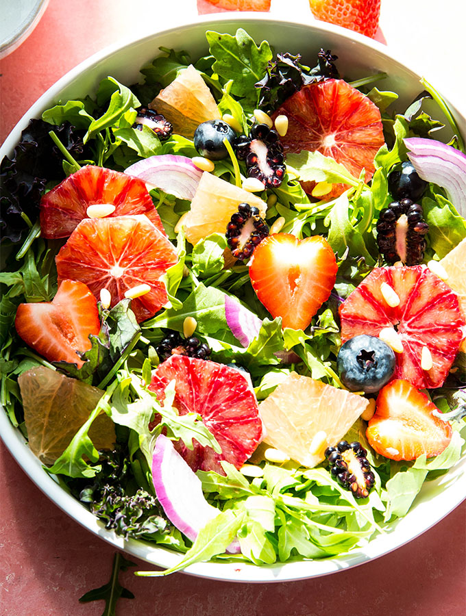 Winter salad is loaded with berries, citrus, onion, and salad dressing.