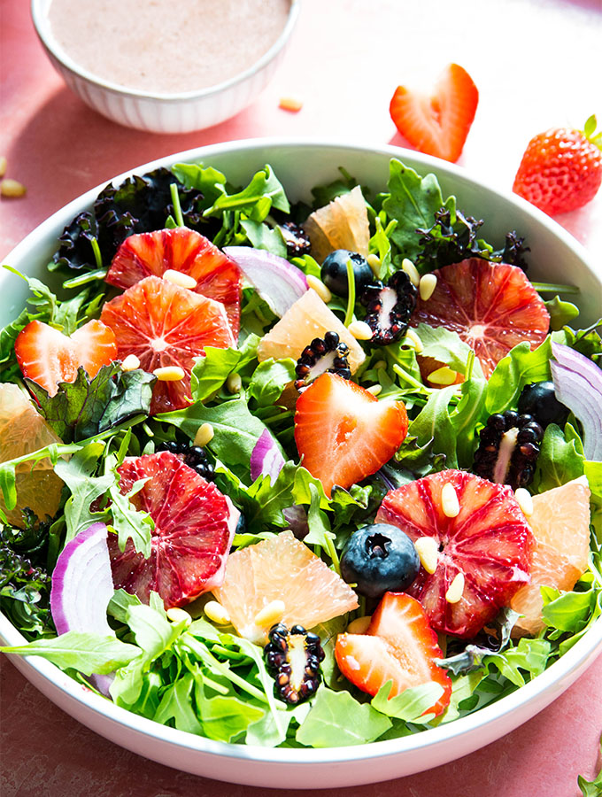 Winter salad is sprinkled with pine nuts and salad dressing.
